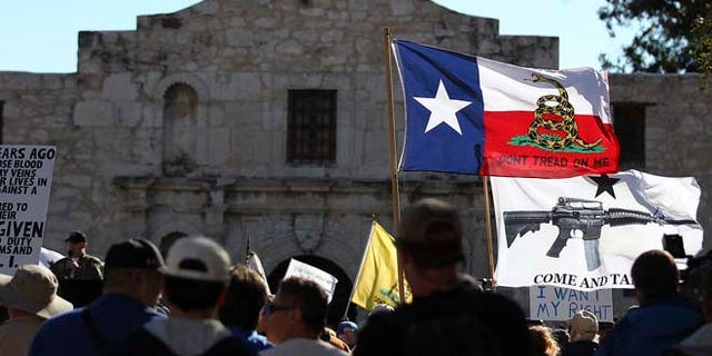 """Oct. 19, 2013: In this file photo, flags fly at the """"Come And Take It San Antonio"""" rally. Long depicted as the rootin'-tootin' capital of American gun culture, Texas is one of the few states with an outright ban on the open carry of handguns. That could change next year, with an expected push for expanding gun rights from the Republican-dominated Legislature."""