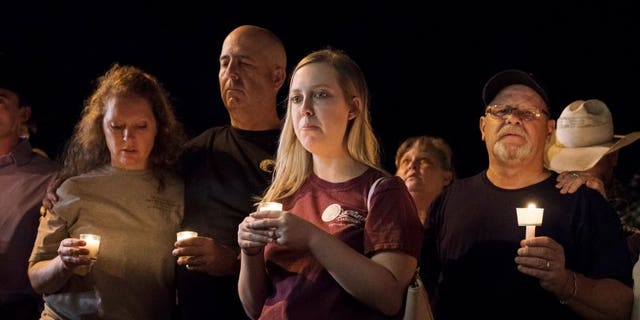 Mourners participate in a candlelight vigil held for the victims of a fatal shooting at the First Baptist Church of Sutherland Springs, Sunday, Nov. 5, 2017, in Sutherland Springs, Texas. (AP Photo/Darren Abate)
