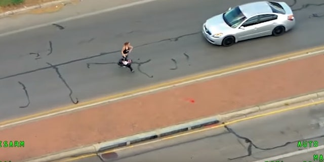 The woman ran with the child through traffic after crashing into another vehicle.