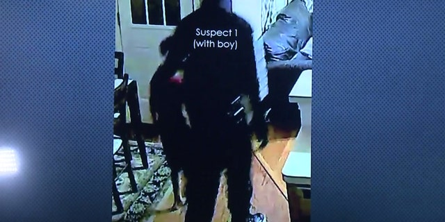 One of the suspects can be seen leading the couple's 7-year-old son around the home looking for money.