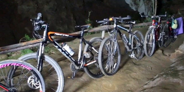 In this image made from video taken Sunday, June 24, 2018, bicycles left from a group of boys who went missing stand parked outside a deep cave in Chang Rai, northern Thailand.