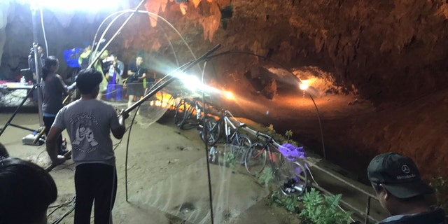 Relatives hold fishing nets, as a symbol to fish out lost spirits inside cave, as a group of locals and relatives perform a ritual calling for those are missing at the entrance of the cave, Tuesday, June 26, 2018, in Mae Sai, Chiang Rai province, northern Thailand.