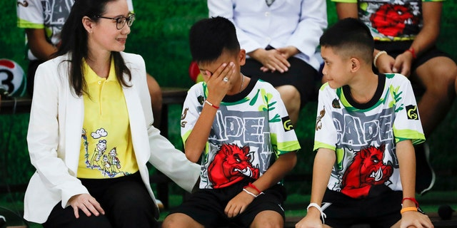 """Rescued soccer player """"Titan"""" Chanin Vibulrungruang reacts after paying respect to a portrait of Saman Gunan, the Thai Navy SEAL diver who died in the rescue attempt."""