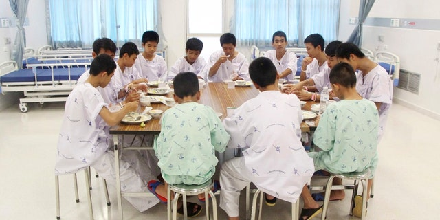 In this Sunday, July 15, 2018, file photo released by Thailand's Ministry of Health and the Chiang Rai Prachanukroh Hospital, some of the rescued soccer team members eat a meal together at a hospital in Chiang Rai, northern Thailand.
