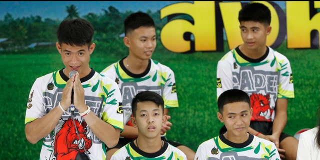 Coach Ekkapol Janthawong, left, and members of the rescued soccer team express their thanks during a press conference discussing their experience of being trapped in a flooded cave.