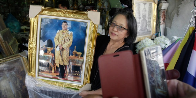 A shopkeeper show portraits of Thailand's Crown Prince Vajiralongkorn to a customer outside of her shop in Bangkok, Thailand, Thursday, Dec. 1, 2016. Thailand is preparing to welcome a new king with final arrangements scheduled to formalize the accession of Crown Prince Maha Vajiralongkorn to the throne. (AP Photo/Sakchai Lalit)