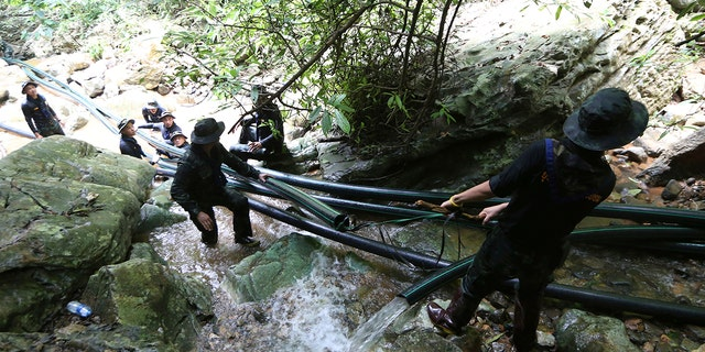 Thai soldiers drag water pipes that will help bypass water from entering a cave where 12 boys and their soccer coach have been trapped since June 23, in Mae Sai, Chiang Rai province, in northern Thailand, July 7, 2018.