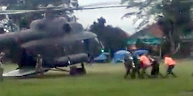 In this image made from video taken Sunday, July 8, 2018, an emergency team carries a stretcher carrying one of the rescued boys from the flooded cave to a waiting helicopter in Mae Sai, Chiang Mai province, northern Thailand.