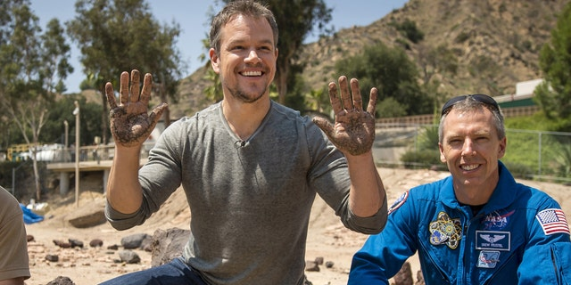 Actor Matt Damon (C) who stars as NASA Astronaut Mark Watney in the film 'The Martian' smiles after having made his hand prints in cement at the Jet Propulsion Laboratory (JPL) Mars Yard, while NASA Astronaut Drew Feustel look on in Pasadena, California in this August 18, 2015.