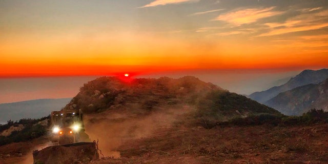 In this photo released by Santa Barbara County Fire Department, a dozer from the Santa Barbara County Fire Department clears a fire break across a canyon from atop Camino Cielo down to Gibraltar to make a stand should the fire move in that direction, Wednesday, Dec. 13, 2017, in the Santa Ynez Mountains area of Santa Barbara, Calif.