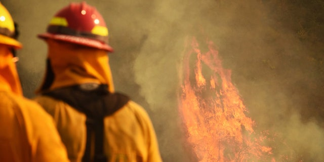 In this photo provided by the Santa Barbara County Fire Department, firefighters keep an eye on flames as pockets of unburned vegetation flare up off Bella Vista Dr. in Montecito, Calif., Wednesday, Dec. 13, 2017.