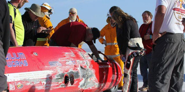 Thompson takes a look at the damage done to her motorcycle after crashing it at 343 mph.