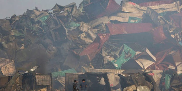 Photographers walk near the deformed remains of containers after an explosion at a warehouse in northeastern China's Tianjin municipality, Thursday, Aug. 13, 2015. Huge, fiery blasts at a warehouse for hazardous chemicals killing many people and turned nearby buildings into skeletal shells in the Chinese port of Tianjin, raising questions Thursday about whether the materials had been properly stored. (AP Photo/Ng Han Guan)