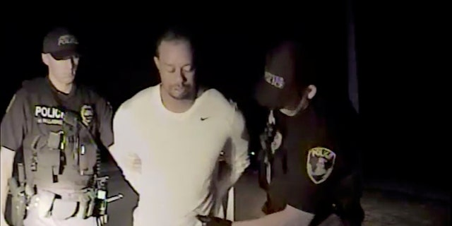 Tiger Woods is seen handcuffed and searched by police officers in this still image from police dashcam video in Jupiter, Florida, on May 29.