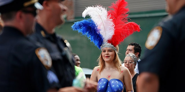 A painted lady in Times Square walks near a group of police officers.