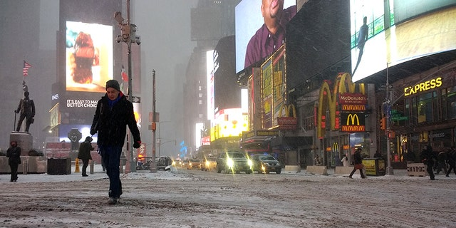 """Pedestrians walk through snow-covered streets in Times Square in New York as a powerful """"bomb cyclone"""" hits the Northeast."""