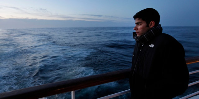 A passenger of MS Balmoral Titanic memorial cruise ship, gazes out to the Atlantic Ocean, following a memorial service, marking the 100-year anniversary of the Titanic disaster, in the early hours of Sunday, April 15, 2012.