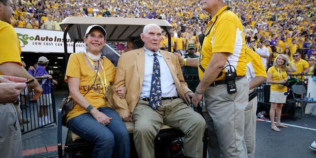 In this Sept. 20, 2014, file photo, NFL great and LSU alumnus Y.A. Tittle, center, arrives in Tiger Stadium in the first half of an NCAA college football game between LSU and Mississippi State, in Baton Rouge, La.