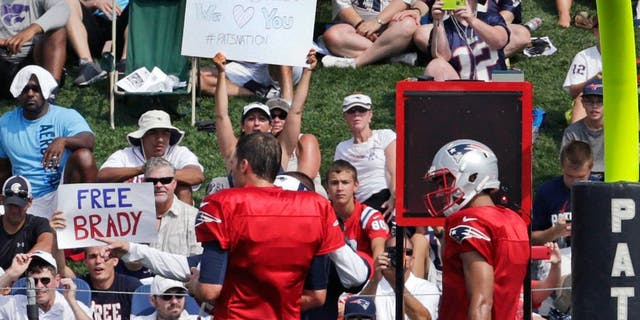 """A fan holds a sign reading """"Free Brady"""" as New England Patriots quarterback Tom Brady, left, prepares to practice with his back-up Jimmy Garoppolo during an NFL football training camp in Foxborough, Mass., Thursday, July 30, 2015. (AP Photo/Charles Krupa)"""