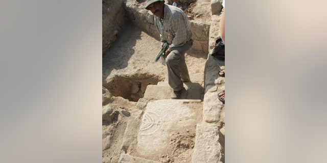 Tomb door with menorah being exposed during excavations at Tiberias in 2010.