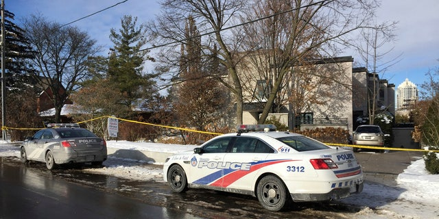 Police cars are parked outside the home of billionaire Barry Sherman on Saturday, Dec. 17, 2017 in Toronto.