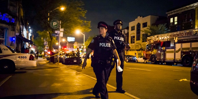 Police secure a perimeter around the scene of a mass shooting in Toronto.
