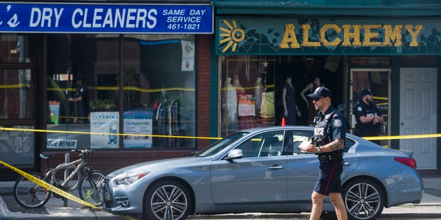Police are photographed investigating a car with a bullet hole within the scene of a mass shooting in Toronto on Monday, July 23, 2018.