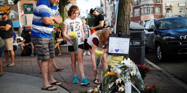People add flowers and messages to a memorial for the victims of Sunday's shooting in Toronto.