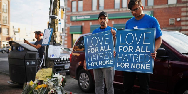 People hold signs at a memorial remembering the victims of Sunday's shooting in Toronto.