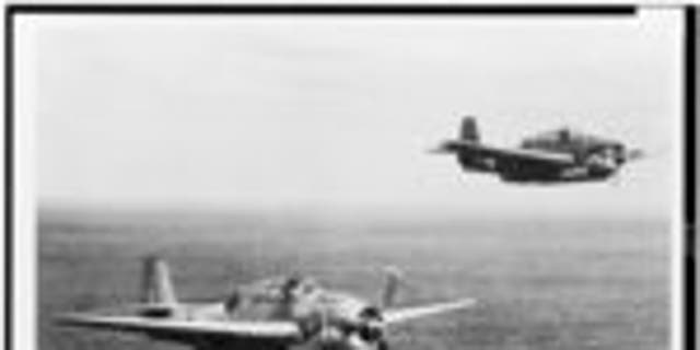 Two U.S. Navy Grumman Avenger torpedo-bombers in flight over the ocean, one having just released a torpedo