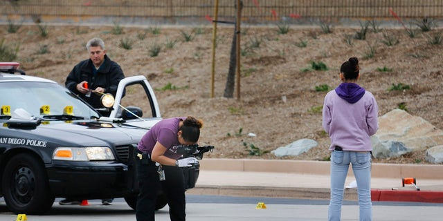 San Diego police investigate the scene of an early Saturday morning shooting. Police say a 15-year-old boy left behind a suicide note before he was killed by police officers after pointing a BB gun at them in a high school parking lot in the dark.