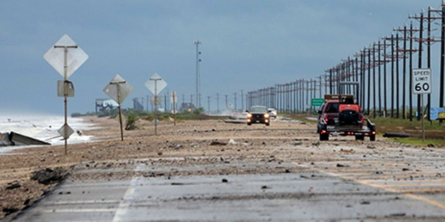 Vehicles navigate past waves and debris washing over in High Island, Texas, as Tropical Storm Cindy approaches Wednesday, June 21, 2017.
