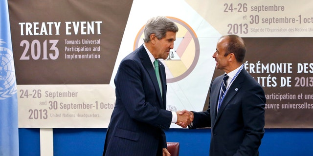 U.S. Secretary of State John Kerry, left, shakes hands with Under Secretary-General for Legal Affairs Miguel Serpa Soares after signing the Arms Trade Treaty.