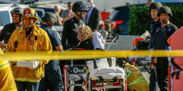 An unidentified woman is helped by paramedics at a triage area after a gunman held dozens of people hostage inside a Trader Joe's store in Los Angeles, July 21, 2018.
