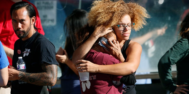 Unidentified Trader Joe's supermarket employees hug after being evacuated by Los Angeles Police after a gunman barricaded himself inside the store in Los Angeles, July 21, 2018.