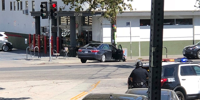 Police officers stand guard near a crashed vehicle outside a Trader Joe's store in the Silver Lake neighborhood of Los Angeles on Saturday.