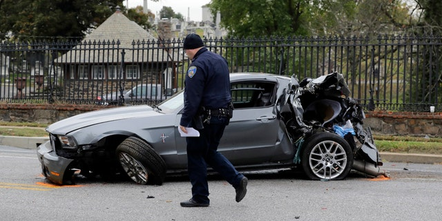 FILE - In this Nov. 1, 2016 file photo, a member of the Baltimore Police Department walks past a car that was damaged by a school bus before the bus was involved in a fatal collision with a commuter bus in Baltimore. A jump in traffic fatalities last year pushed deaths on U.S. roads to their highest level in nearly a decade, erasing improvements made during the Great Recession and economic recovery, a leading safety organization said Wednesday, Feb. 15, 2015.  (AP Photo/Patrick Semansky. File)