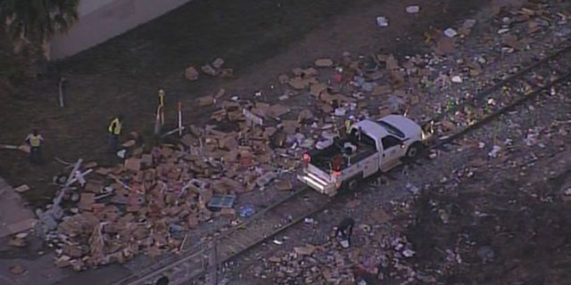 A train colliding with a semi-truck left boxes of meat scattered all over the roadway.