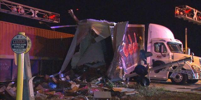 The semi-truck split in two when the train struck it.