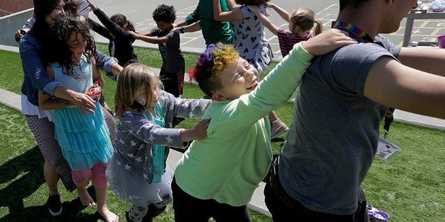 Campers and camp counselors dance at Rainbow Day Camp.