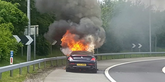 Andrew Lindsay's BMW bursting into flames.  A DAD-of-one's BMW 6 Series erupted in a fireball on a motorway and trapped him inside the burning car – when the locks jammed.  See NTI story NTIBMW.  Andrew Lindsay, 45, desperately tried to escape the motor when it burst into flames while he was travelling at 70mph on the M6 Toll Road.  He managed to shoulder barge the driver's door open and leap from the car moments before the engine exploded and melted the tyres to the road.  Andrew, a copy editor from Whittington, Staffs., was on his way to see family in North Wales when the blaze broke out on June 1.