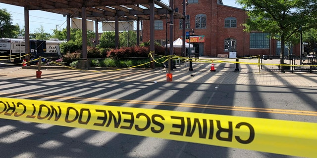 Police crime-scene tape keeps people away from the brick Roebling Wire Works building, background, in Trenton, N.J., hours after a shooting broke out there at an all-night art festival.