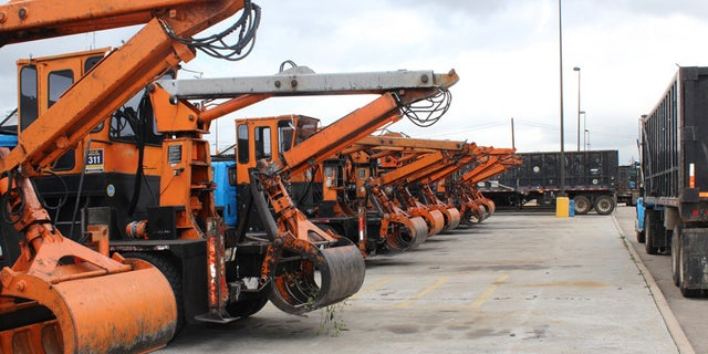 A row of debris scooper trucks in Houston, waiting to go out in the field.