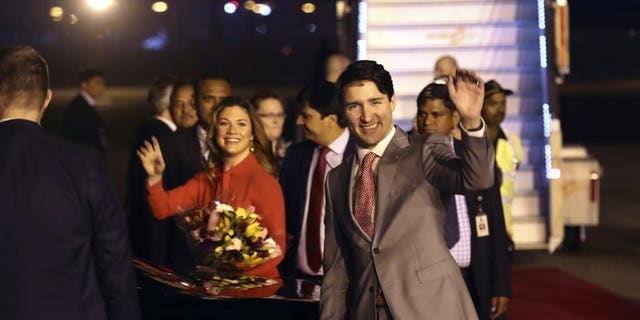 Canadian Prime Minister Justin Trudeau and his wife, Sophie Gregoire Trudeau, wave upon their arrival in New Delhi, India, Feb. 17, 2018.