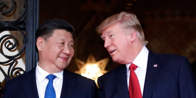 FILE - In this April 6, 2017 file photo, Chinese President Xi Jinping, left, smiles at U.S. President Donald Trump as they pose together with their wives for photographers before dinner at Mar-a-Lago in Palm Beach, Fla.