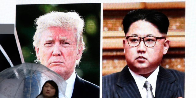 A woman walks by a huge screen showing U.S. President Donald Trump, left, and North Korea's leader Kim Jong Un, in Tokyo, Friday, March 9, 2018. After a year of threats and diatribes, U.S. President Donald Trump and third-generation North Korean dictator Kim Jong Un have agreed to meet face-to-face for talks about the North's nuclear program