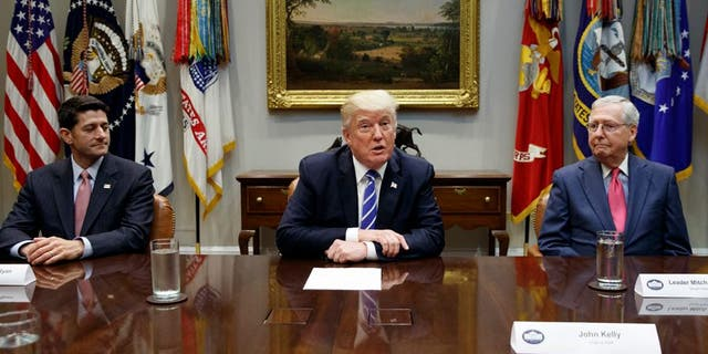 President Trump sits at the White House with House Speaker Paul Ryan and Senate Majority Leader Mitch McConnell to talk taxes last month. The tax bill passed both the House and the Senate on Tuesday.