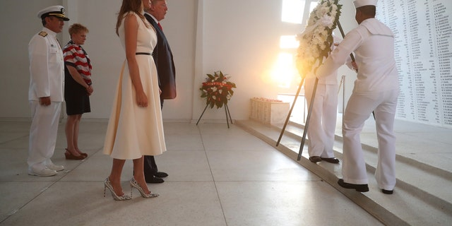 President Donald Trump and first lady Melania Trump watch as a wreath is positioned at the USS Arizona Memorial at Pearl Harbor, Hawaii, Nov. 3, 2017.