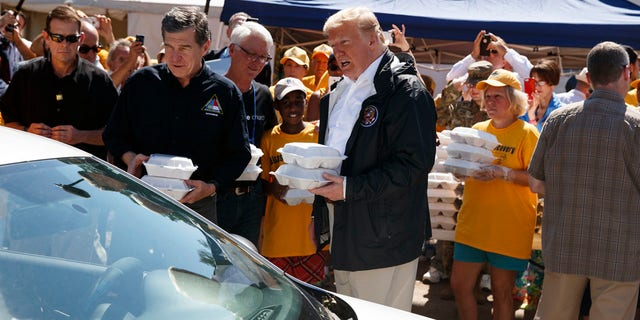 Trump and North Carolina Gov. Roy Cooper hand out packaged meals in New Bern.