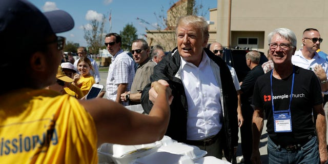 President Trump shakes hands with a volunteer at the Temple Baptist Church in New Bern, N.C. Wednesday.
